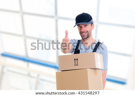 friendly postman with parcels and thumb up looking friendly - stock photo