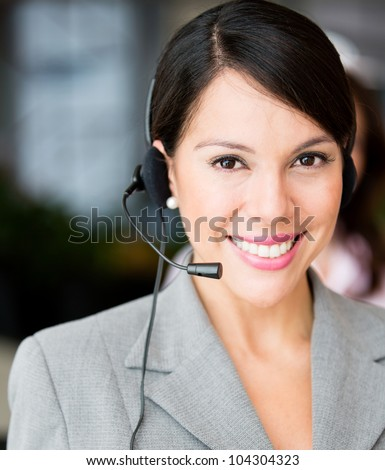 Friendly receptionist smiling and wearing a headset - stock photo