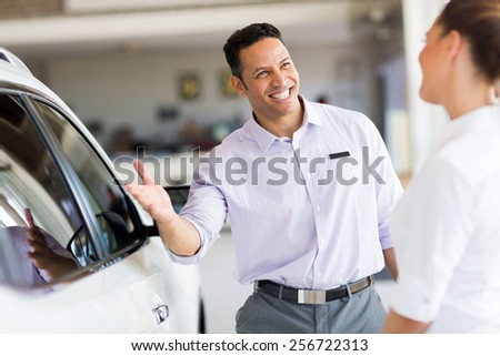 friendly salesman selling car to a customer in showroom - stock photo