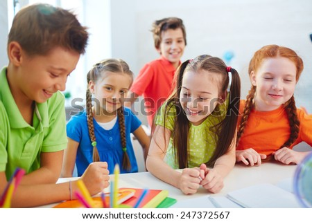 Friendly schoolkids working in team at lesson - stock photo