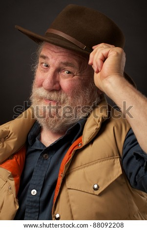 Friendly senior man tipping his hat - stock photo