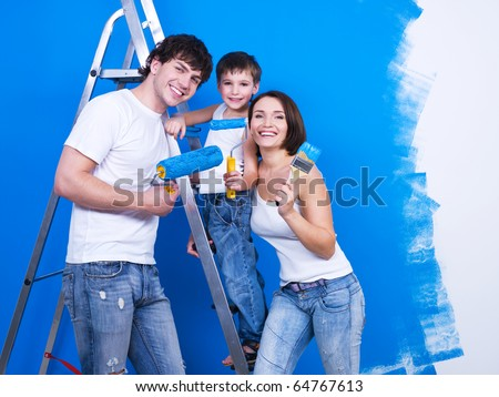 Friendly smiling family with young son painting the wall - stock photo