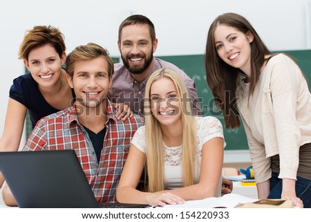 Friendly smiling group of young male and female college or university students grouped together around a laptop computer posing for the camera - stock photo