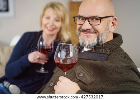 Friendly smiling middle-aged man enjoying a glass of red wine at home while relaxing on the sofa with his wife, close up head and shoulders - stock photo