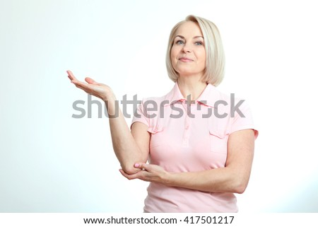 Friendly smiling middle aged woman pointing at copyspace isolated on white background - stock photo