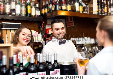 Friendly smiling people working in a popular bar. A barista, bartender and a waitress - stock photo