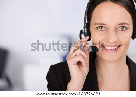 Friendly smiling receptionist, personal assistant or call centre operator , head and shoulders close up portrait with copyspace - stock photo