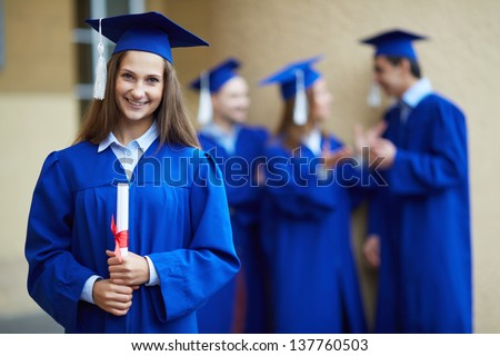 Friendly students in graduation gowns talking with happy girl in front - stock photo