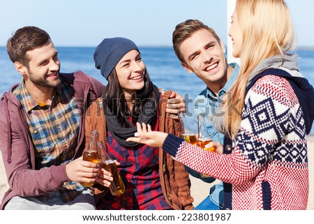Friendly talk. Four happy friends talking to each other and smiling while sitting on the beach and drinking beer  - stock photo