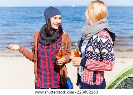 Friendly talk. Two beautiful young women drinking beer and talking to each other while standing near their tent on the riverbank - stock photo