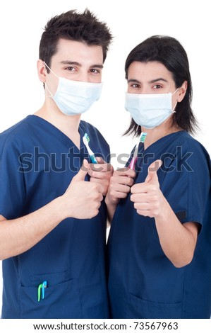friendly team of dentists, doctors holding toothbrush and showing thumb up sign isolated on white background - stock photo