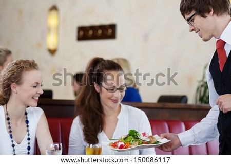 Friendly waiter serving a salad platter to two attractive young women friends sitting together enjoying a meal in a restaurant - stock photo
