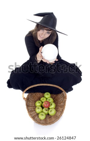 Friendly witch treading us on a basket of apples while looking in her crystal ball - stock photo