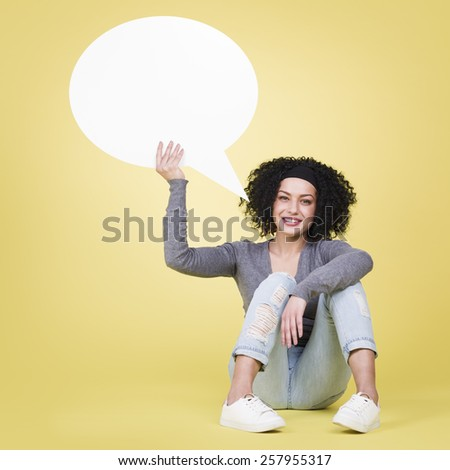 Friendly woman being joyful holding a white blank speech bubble with empty copy space, isolated on yellow background. - stock photo