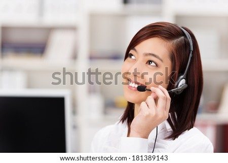 Friendly young Asian call centre operator chatting on the headset phone and smiling as she listens to the customer speaking as she tries to assist - stock photo