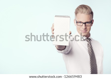 Friendly young businessman showing blank notepad with space for text, isolated. - stock photo