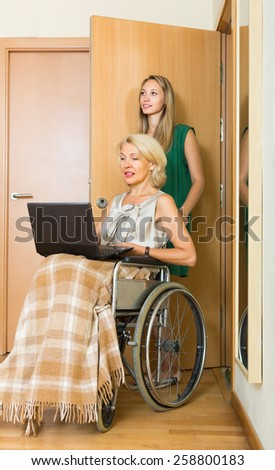 Friendly young social worker and disabled mature woman on chair with laptop. Focus on mature woman - stock photo