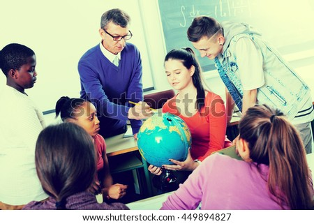 Friendly young students and teacher sitting and talking in the classroom while the break - stock photo