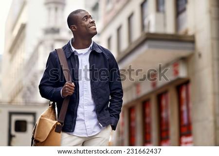 Friendly young trendy african black man walking around the urban city having fun - stock photo