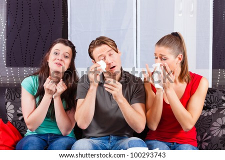 Friends - a man an two women - watching a sad movie in TV - stock photo