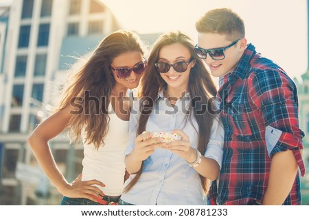 Friends amazed watching the smart phone outdoor - stock photo