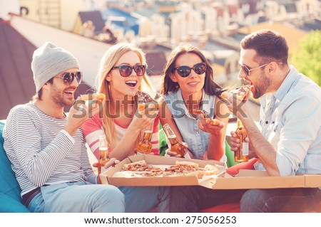 Friends and pizza. Four young cheerful people eating pizza and drinking beer while sitting at the bean bags on the roof of the building - stock photo