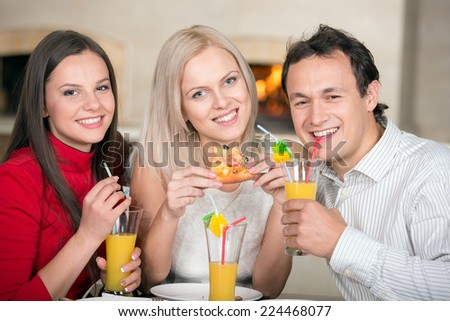 Friends are drinking juice and eating pizza in the pizzeria. Close-up. - stock photo