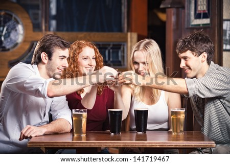 Friends at a bar cheering some shot glasses. - stock photo