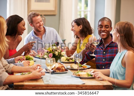 Friends At Home Sitting Around Table For Dinner Party - stock photo