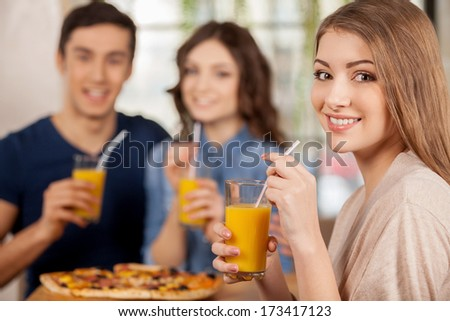 Friends at the restaurant. Three cheerful young people eating pizza at the restaurant while beautiful woman looking over shoulder and smiling - stock photo