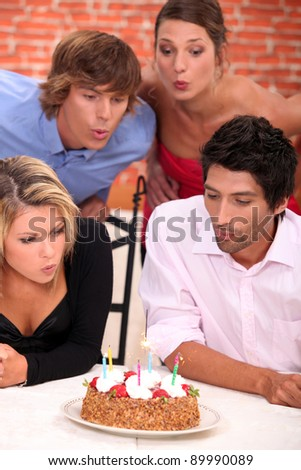 Friends celebrating a birthday together - stock photo