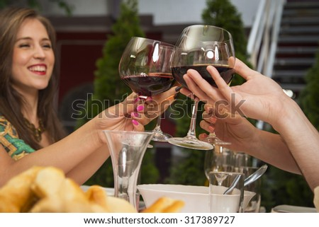 Friends celebrating and toasting with wine during a lunch at a restaurant. - stock photo