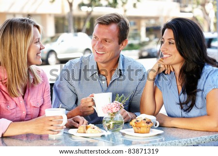 Friends chatting outside caf - stock photo