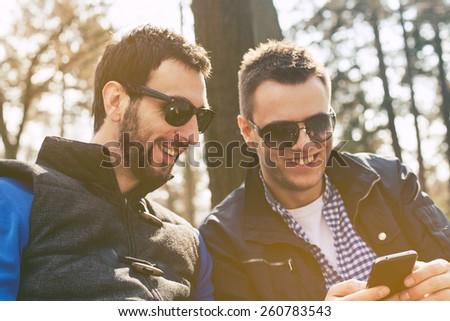 Friends chatting with their smartphones - stock photo