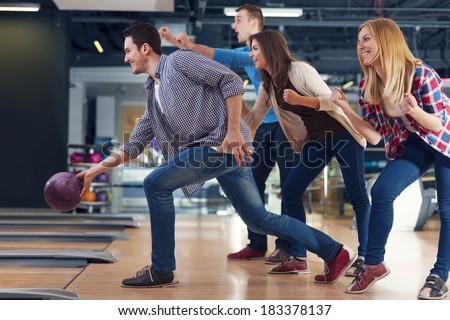 Friends cheering their friend while throwing bowling ball   - stock photo