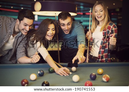 Friends cheering while their friend aiming for billiards ball - stock photo