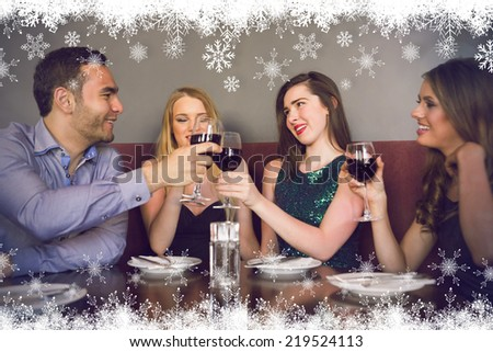 Friends clinking red wine glasses at a bar against fir tree forest and snowflakes - stock photo