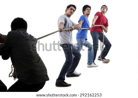 Friends competing in game of tug of war together - stock photo