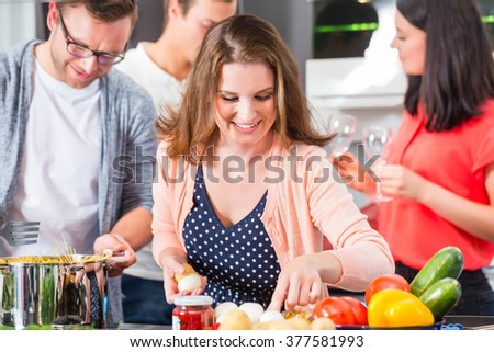 Friends cooking pasta and meat in domestic kitchen - stock photo