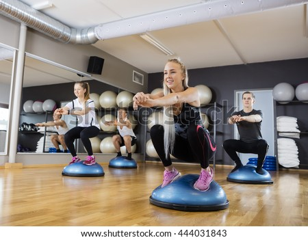 Friends Doing Squatting Exercise On Bosu Ball In Gymnasium - stock photo