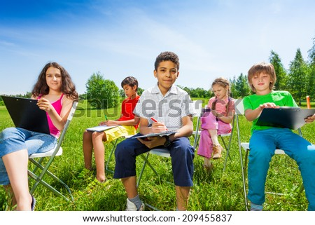 Friends draw with clipboards and sit on chairs - stock photo