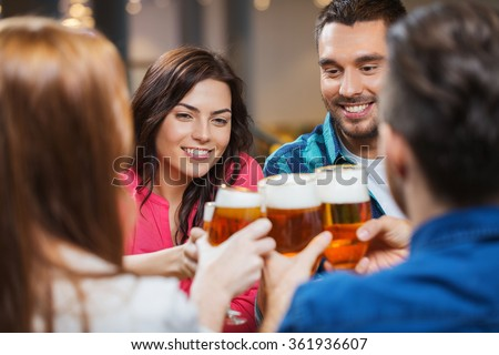 friends drinking beer and clinking glasses at pub - stock photo