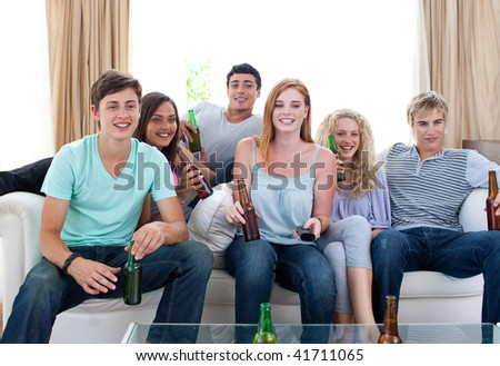 Friends drinking beer and watching tv at home - stock photo