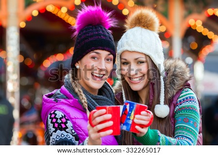 Friends drinking eggnog on Christmas Market  - stock photo