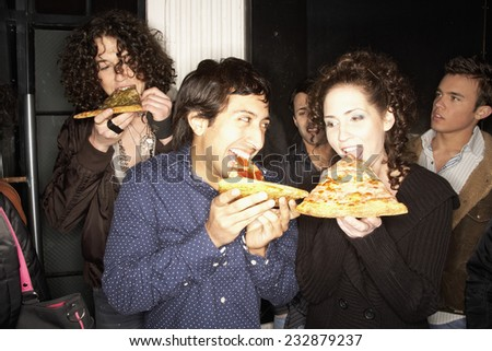 Friends Eating Pizza Slices While Waiting in Line - stock photo