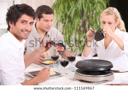 Friends eating raclette - stock photo