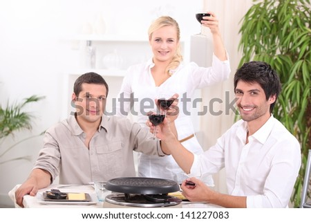 Friends enjoying a raclette - stock photo