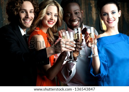 Friends enjoying champagne or wine in a party, great bonding. - stock photo