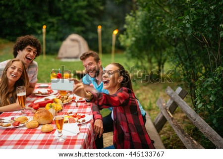 Friends enjoying picnic day and making selfie together. - stock photo