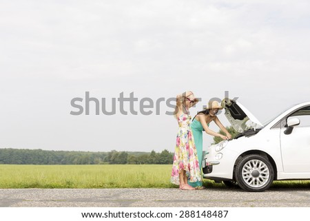 Friends examining broken down car on country road against clear sky - stock photo